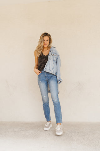 Woman wearing a Zsupply skimmer tank top in black with a denim jacket