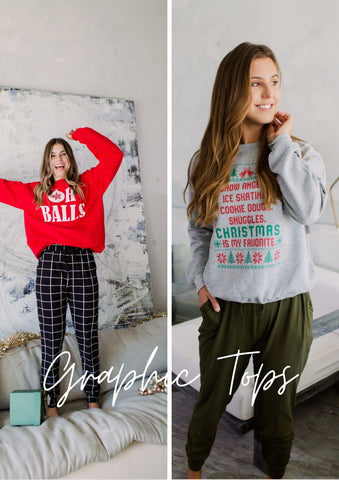 Two girls wearing graphic Christmas Sweatshirts