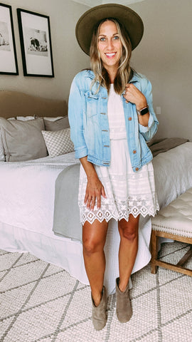 Woman wearing a white summer dress with a jean jacket, felt fedora and booties for Fall