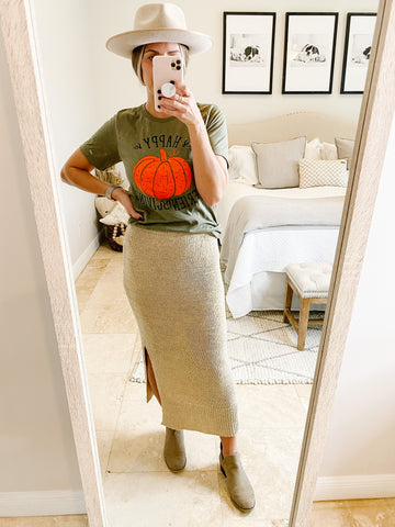 Woman wearing a happy friendsgiving t-shirt with knit midi skirt and booties.