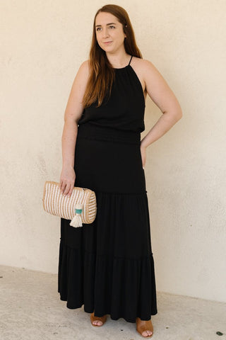 woman wearing a black maxi dress for a wedding dress style guide.
