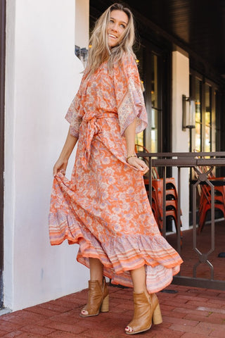Woman wearing a bohemian orange and blue maxi dress for a wedding guest style guide.
