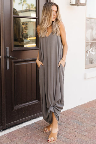 woman wearing a grey maxi dress for wedding guest style guide.