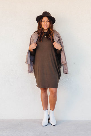 Woman wearing a olive dolman dress with white booties and fedora