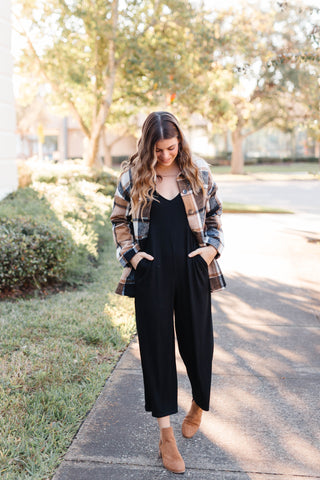 Woman wearing a black jumpsuit with a plaid shacket