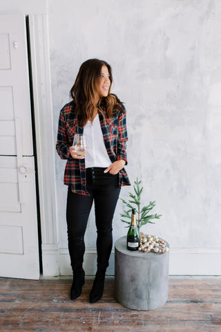 Woman wearing a white shirt, open flannel shirt with dark denim skinny jeans