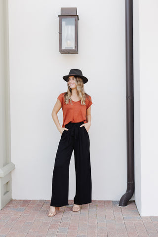 Woman wearing a rust colored tee and black high waisted wide leg pants