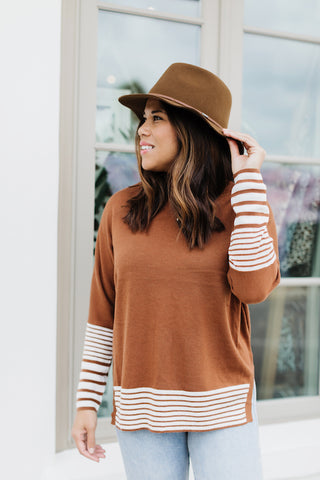 Woman wearing a dolman rust and cream sweater with felt fedora