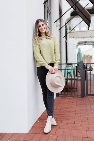 Girl wearing black denim jeans with bright green sweater.
