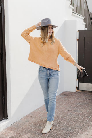 Girl wearing high waisted straight leg jeans with bright orange sweater.