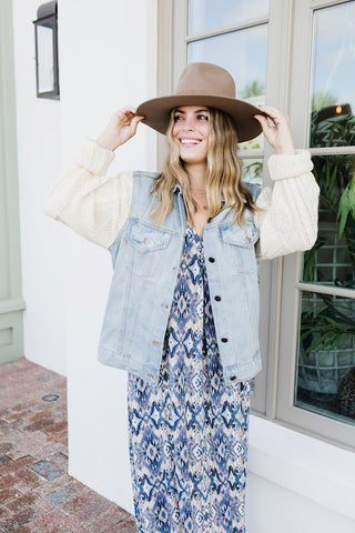Girl wearing a denim jacket with sweater sleeves and fedora felt hat