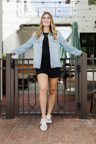Girl wearing a black romper with a light denim jacket over top.