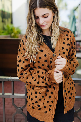 Girl wearing a rust and black leopard oversized cardigan