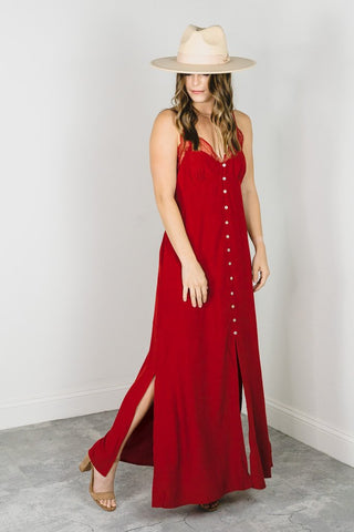 Woman wearing a red lace maxi dress for a wedding guest style guide