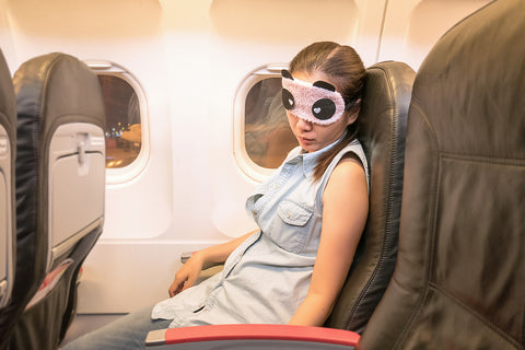 photo of a young woman taking a nap on a plane at night.