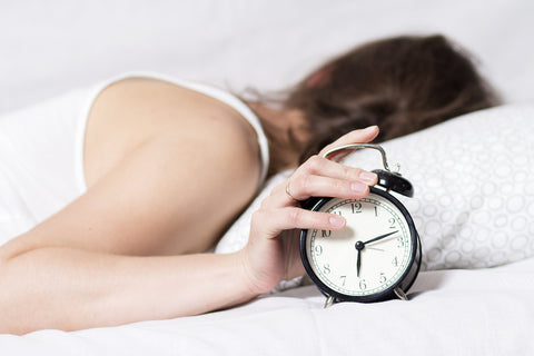 photo of a woman turning off her alarm clock because she is trying to sleep.