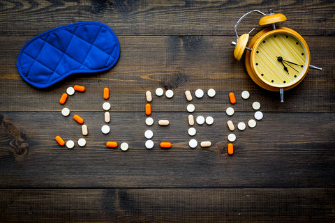 "The word ""sleep"" written out in pills with a sleep mask and an alarm clock."