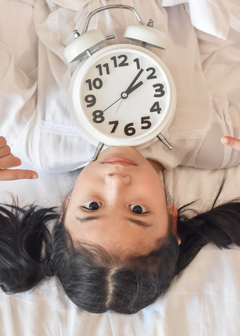 photo of little asian girl with clock.