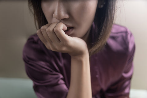close up shot of woman biting nails.
