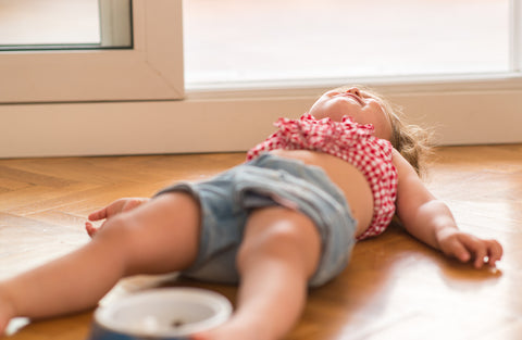 toddler laying on the ground during a tantrum.