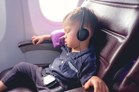 tiny child flying on an airplane. He's sleeping in the seat with headphones on.