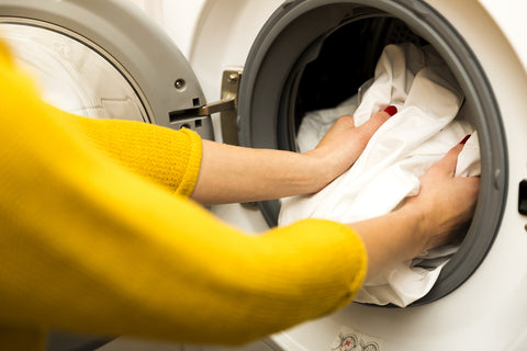 close up photo of a woman putting a sheet into a front loading washer.