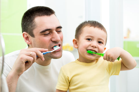 photo of father and son brushing their teeth together.