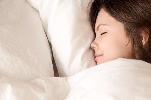 image of woman cuddled up in blanket sleeping.