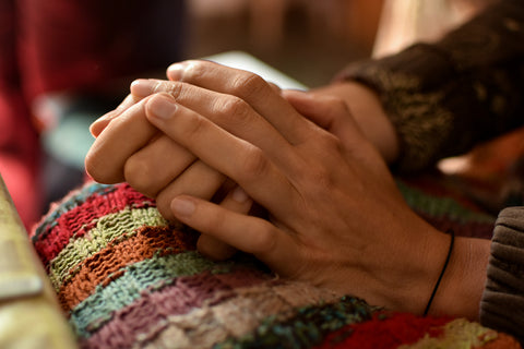 hands clasped together on top of a knitted blanket.