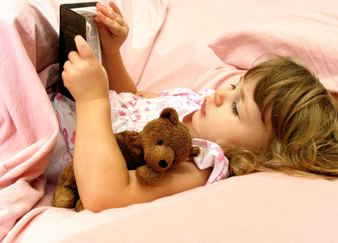 photo of a young girl reading her bible before sleep.