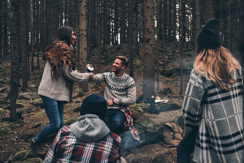 photo of a group of friends laughing around a campfire.