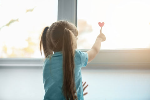 young girl touching heart on window.