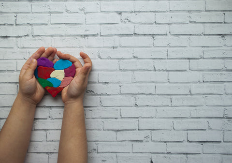 child's hands holding a patchwork heart on a brick wall backdrop.