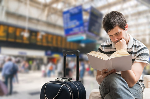 photo of a man reading a book at train station.