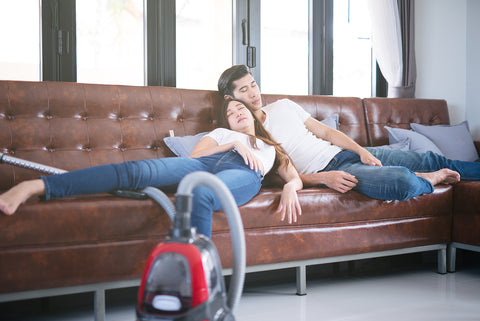 Photo of a young couple napping on the couch.