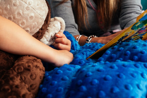 close up photo of a girl holding a stuffed animal under a weighted blanket.