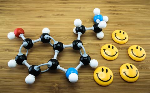 photo of serotonin molecule and happy faces.