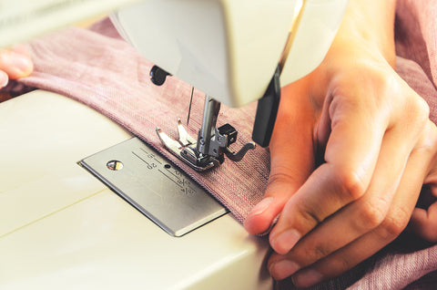 photo of a sewing machine and a hand sewing fabric.
