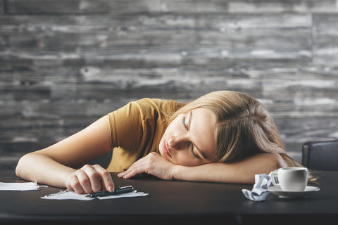 young woman sleeping with a small espresso and pen in her hand.