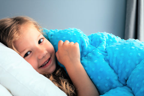 A photo of a happy child using a weighted blanket.