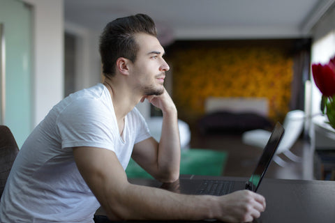 photo of a man sitting in front of a laptop staring in the distance.