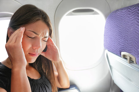 photo of a woman holding her head on an airplane.