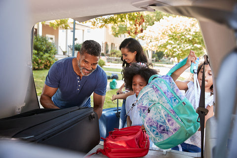 photo of a family packing up their trunk with suitcases.