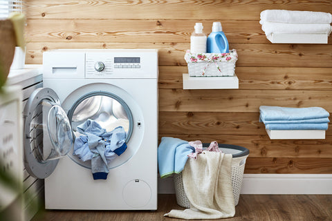 photo of a front load dryer and laundry spilling out in a laundry room.
