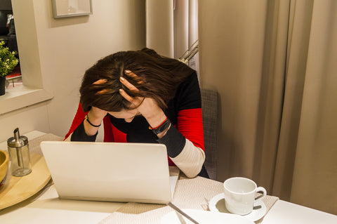 photo of a woman holding head in front of laptop.