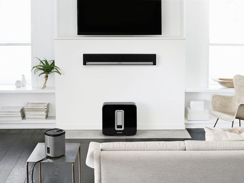 A Sonos SUB placed on the ground in a Living room setting with  mounted Playbar below a wall mounted TV, Lounge shelf on its side and a lounge sofa with a speaker on a side table