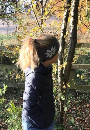 9 year old girl wearing grey wool headband with white pattern seen from the side