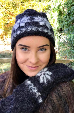 Beautiful girl wearing black brushed wool hat and mittens with white nordic pattern