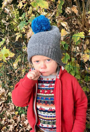 small boy wearing a grey wool hat with turkish pom