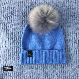 Blue wool kids hat with grey fur pom pom laying on a light blue wool blanket Varma wool